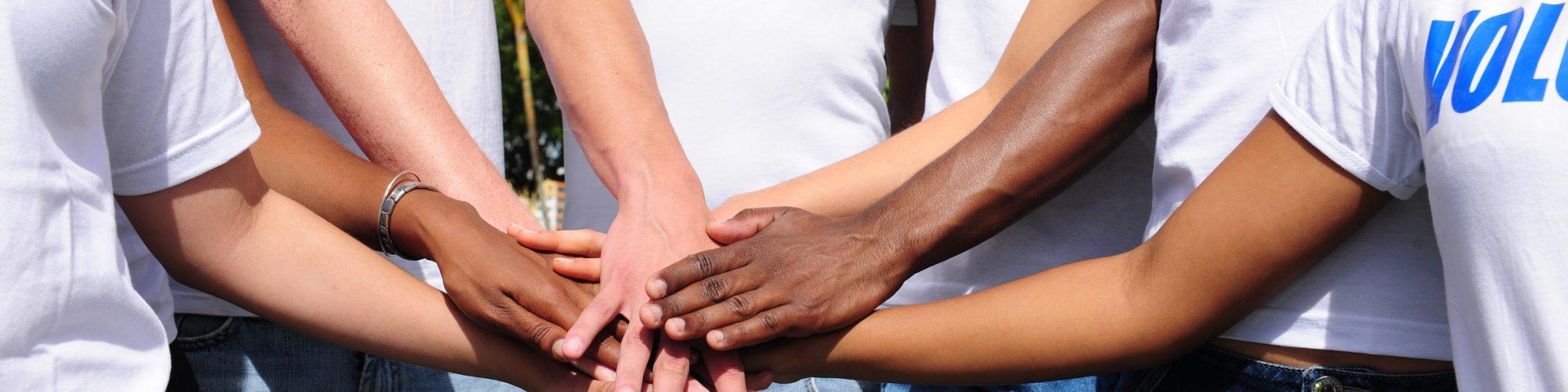 multi-ethnic volunteer group hands together showing unity